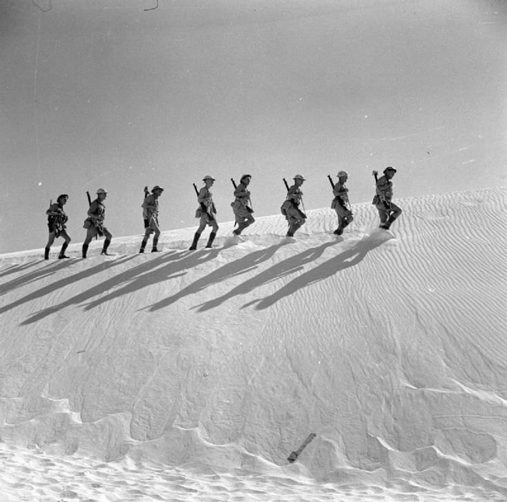 DEC 21 December 1941 South Africans under night air attack in the Desert. An official publicity shot of a South African rifle section patrolling the desert sand dunes.
