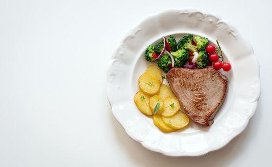 Roasted tuna steak with garnish, top view