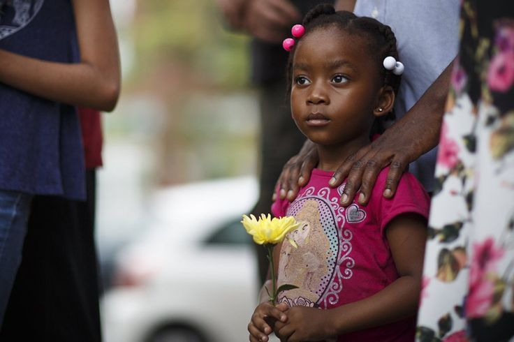 Fifi Brittany holding a flower at the vigil.  Members of immigrant communities and their friends and loved ones gathered for a vigil at St. Francis of Assisi Catholic Church in Harrisburg in reaction to a recent Supreme Court decision relating to the Deferred Action for Parents of Americans (DAPA) program.  Monday, June 27, 2016.  Daniel Zampogna, PennLive