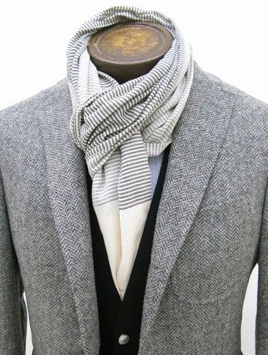 Trendy mannequin display featuring grey tweed jacket, blue vest and a white and grey striped scarf.