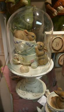 glass dome cloche bunny and teacups decoration. Two little bunnies playing in three tea cups with spring colored eggs. Displayed on a pedestal base with a glass dome cover.