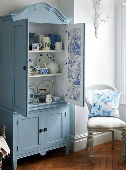 Beautiful blue cabinet with wallpaper lining set within a pure white room, simply lovely.