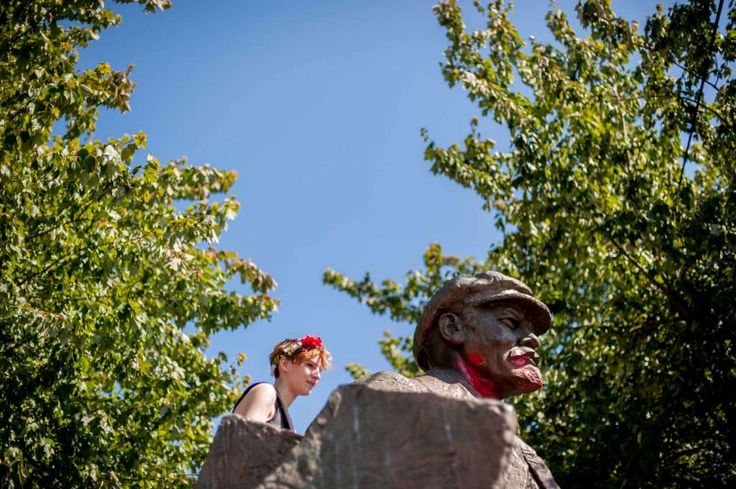 A woman climbs a statue of Vladimir Lenin during the 27th annual Fremont Solstice Parade, photographed Saturday, June 20, 2015, in Seattle, Washington. As part of the Fremont Fair, the parade set the tone for the first day of summer on June 21. Seattle Mayor Ed Murray and a handful of President Donald Trump's most ardent supporters agree: It's time for Fremont's statue of Vladimir Lenin to come down.