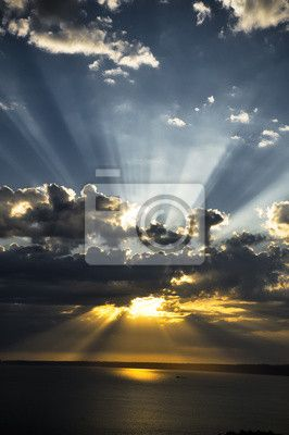 Wall Mural sunrays at sunset with clouds lights trace sunbeams.