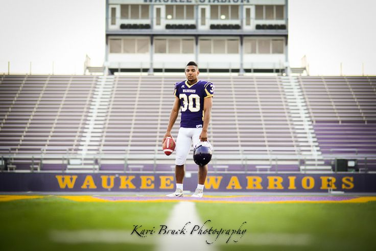 Kari Bruck Photography 2015 high school senior session pose idea for football players. High school senior boy inspiration for posing for football. Senior Pictures in a guy in his full football uniform in front of stadium. Sports or Sport pictures.