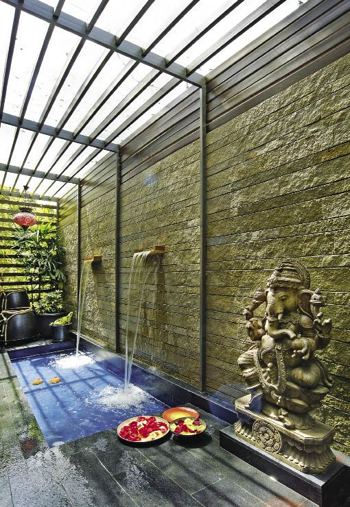 Cabin deck: The office cabin is edged with a lovely pool of water, a water cascade, a wooden Ganpati idol from Tamil Nadu, and plants soaking in soft sunlight through a pergola covered with a glass sheet.