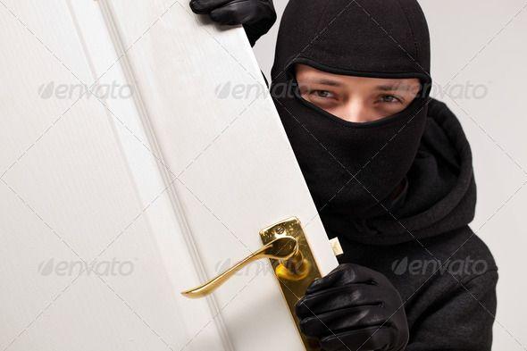 Burglar sneaking in a open house door. http://photodune.net/item/burglar-sneaking-in-a-open-house-door/6213678