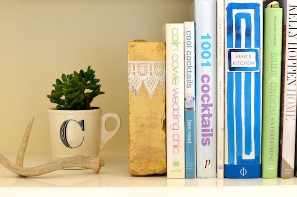use dois tijolos pintados com tinta spray na cor dourada para apoiar e aparar os seus livros nas estantes de forma eficaz e decorativa