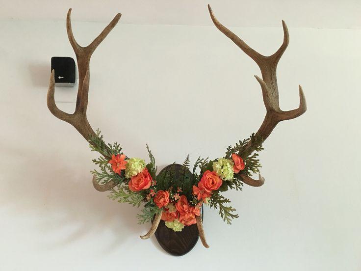 Cuernos de ciervo decorados por flores y helechos artificiales.