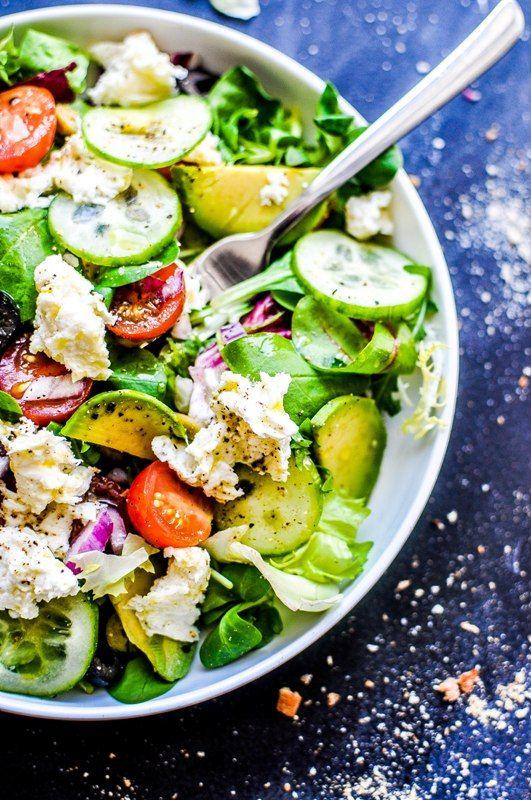 Fresh garden salad with avocado, mozzarella, and tomatoes.