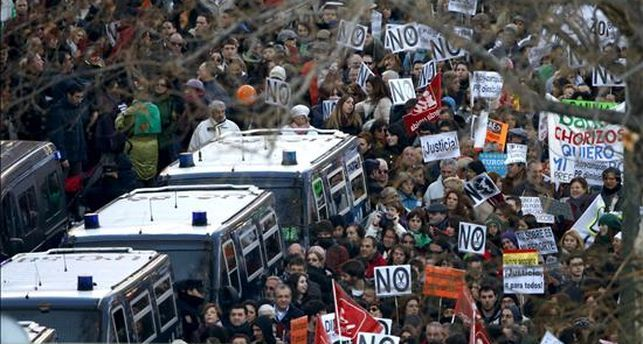 Furgones policiales rodeados de manifestantes en Neptuno / Foto: EFE