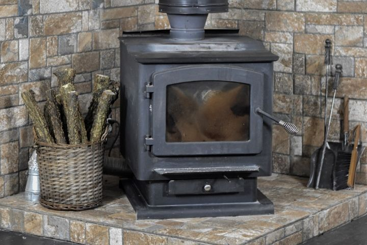 Black Wood Burning Fireplace With Wicker Basket To The Left Holding Wood Logs In 2020 Wood Burning Stove Faux Fireplace Mantels