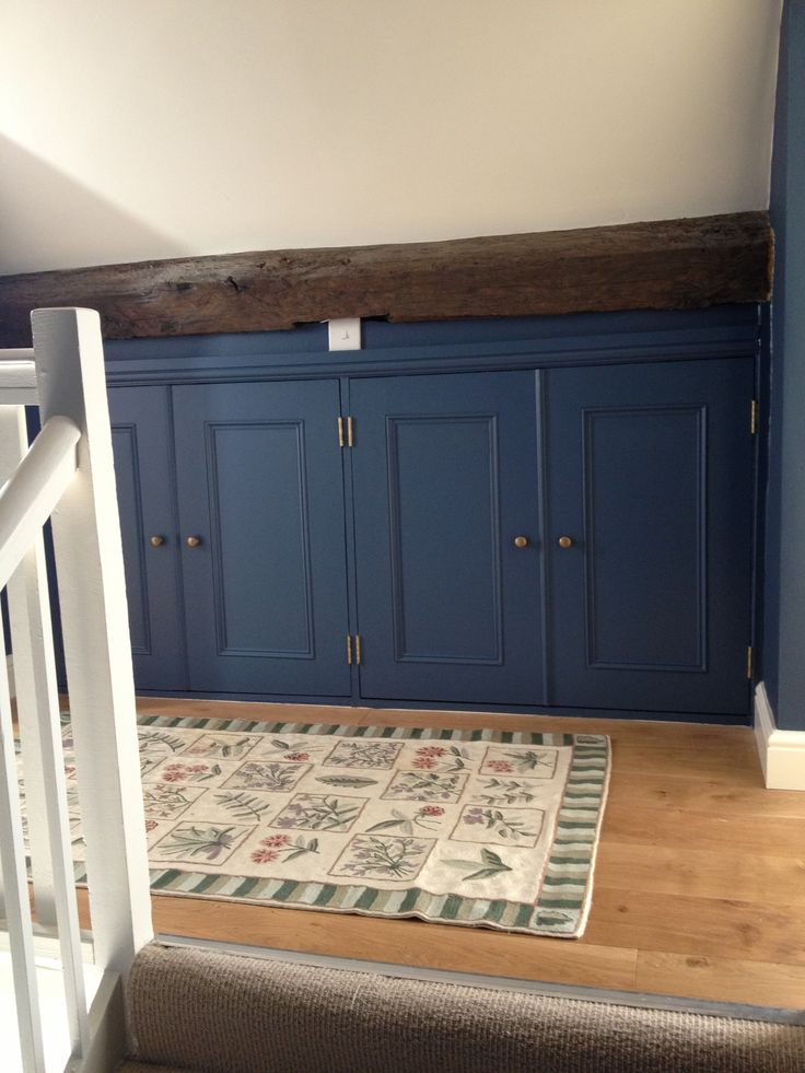Eaves cupboards constructed in blockboard and mdf. Painted in Little Greene dark blue eggshell.