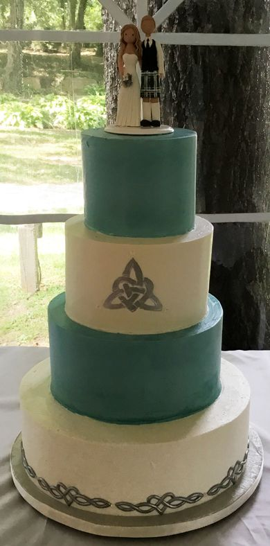 4 Tier Celtic/Irish themed wedding cake, iced  with teal & ivory buttercream & decoroated with silver Celtic love knots delivered at…