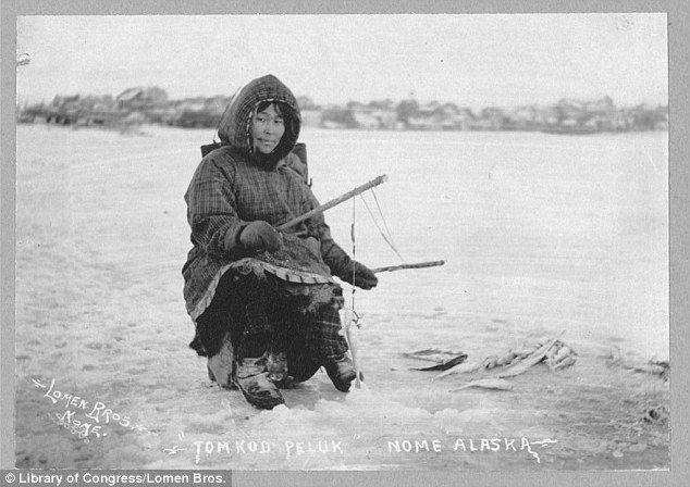 La pêche sur glace: Une femme pose sur un trou de pêche sur la glace, plusieurs poissons succès vu à son côté gauche