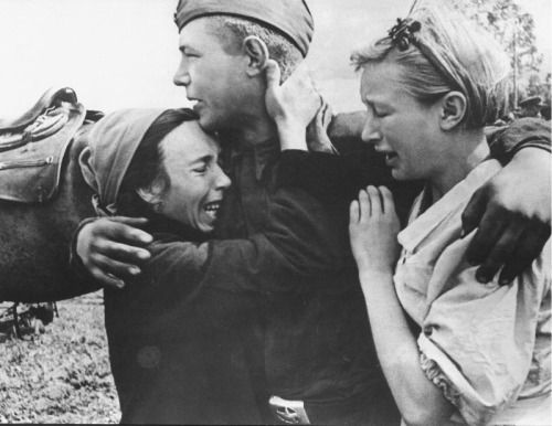 A Soviet soldier embraces family members before being deployed to the front. Bryansk, Soviet Union. 1943.