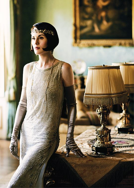 Lady Mary in evening attire with jeweled headband, crystal earrings and long single stranded necklace.
