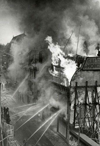 Steden. Uitslaande brand bij de winkel Galerie Modern. Beneden op straat staan de brandweerlieden met minstens acht brandspuiten te blussen. Boven de gebouwen stijgt een zwarte rook op. Utrecht, Nederland, 1939.