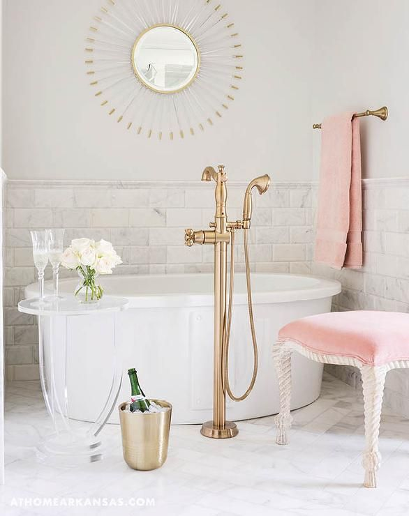 White and pink bathroom features a lucite sunburst mirror place over a freestanding soaking bathtub and a brass floor mount vintage tub filler placed atop a white marble herringbone tile floor.