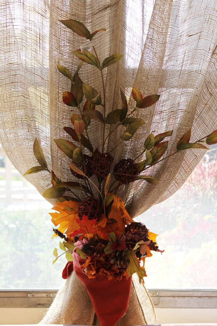 A cute window treatment.... burlap panels, tied with napkins, accented with fall stems...