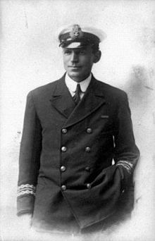 Man in dark naval uniform and wearing an officer's cap