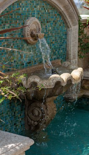 Wall fountain over the fishpond. acrylic privacy screen all around the patio.