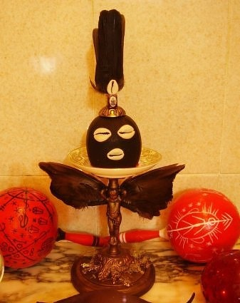 """Voodoo: Eleggua altar - gives us assistance when we are at a """"crossroads"""" and a tough decision must be made. Images of Him are commonly kept behind the front door. Large Ellegua Head may also be used as a candle holder."""