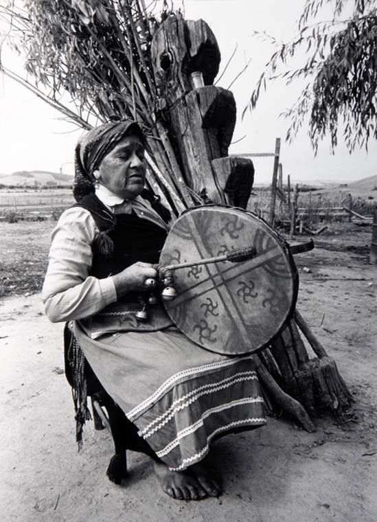 Machi with her kultrún (sacred drum painted with the Directions and stars) seated next to a rewé, which is both a pillar of ancestral spirits and a ladder into other worlds. Among the Mapuche of Chile, women predominate as medicine people.