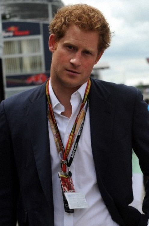 Britain's Prince Harry walks through the paddock area ...
