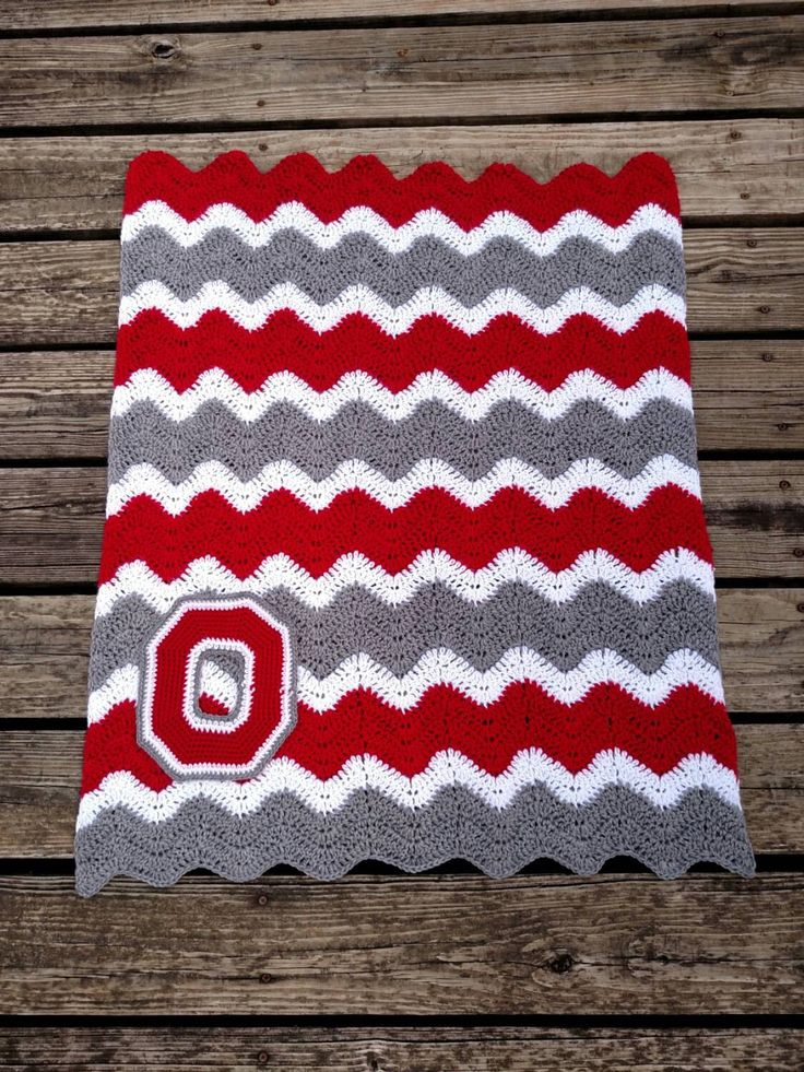 Ohio State Buckeyes inspired crochet chevron blanket! Available in 3 standard sizes but I can customize any size for cribs, beds, strollers, etc. Want another color? Please contact me! I love special orders! Makes a great gift or keep yourself warm whilst rooting for your Ohio State Buckeyes! Hand-made blanket in Ohio State Buckeyes colors. Double crocheted chevron stripes in scarlet, grey, and white. Blanket is made from a soft acrylic yarn and is available in a baby blanket size that…