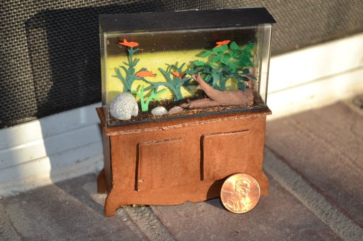 1:12 scale fish tank for a doll house made out of a tic tac box, air drying clay, loose leaf tea, and carboard