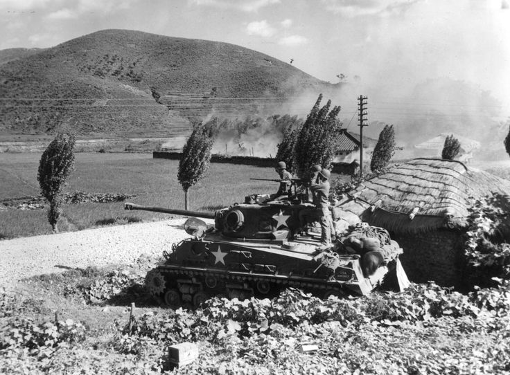 An American Army tank firing on enemy positions in the area around Masan in Korea, 16th August 1950.