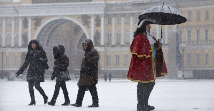 """Homem vestido como czar russo """"Pedro, o Grande"""" anda na neve na praça Dvortsovaya, em São Petersburgo, na Rússia. Os termômetros no local marcam -1º C.   Fotografia: Dmitry Lovetsky/AP."""