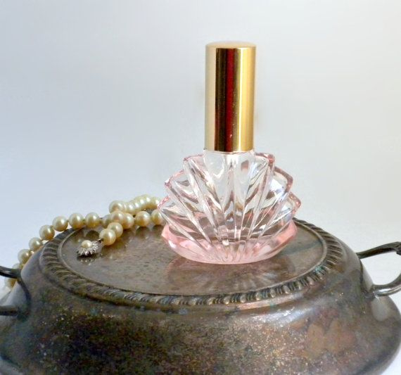 This is a vintage pink Art Deco style glass refillable perfume, or cologne, spray bottle with a gold chrome finish. Its label reads Giraffe