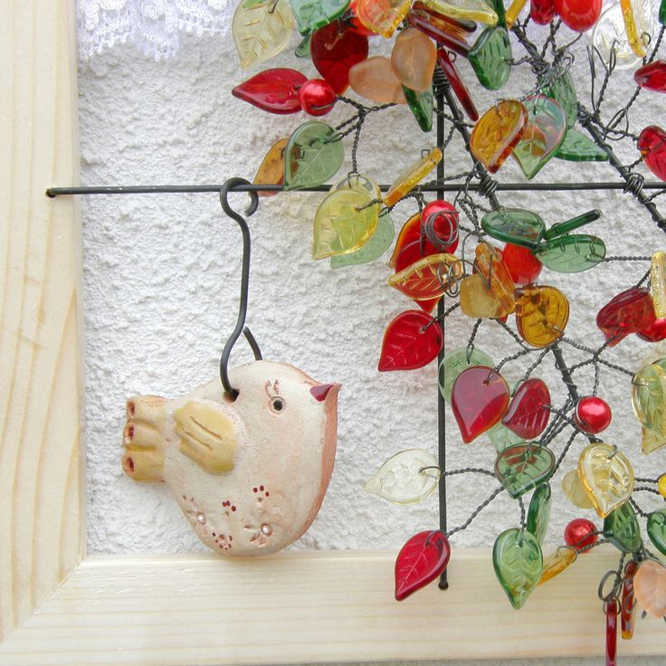 Pohled do okna - Ve stínu šípků Obrázek imitující pohled do okna. Dřevěné okénko o velikosti 21x24 cm z přírodného nelakovaného dřeva a v něm z černého železného drátu udrátovaná větev stromu -skleněné lístečky v barvě zelené, žluté, červené, oranžovéa červené skleněné kuličky a ručně vinuté šípky od Ivanky Hujerové. V okně sedí krásný ...