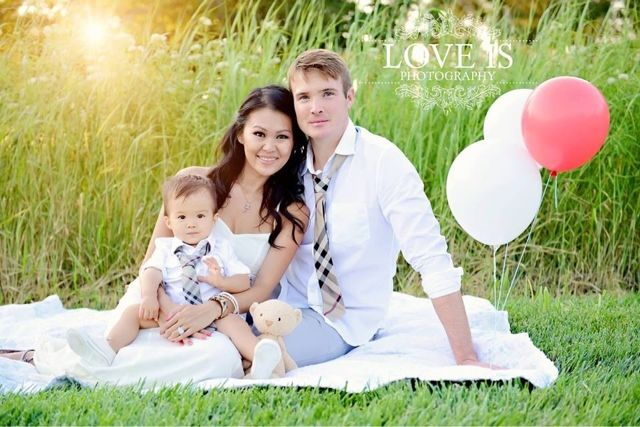 V's first birthday family picture in a field with tall grass
