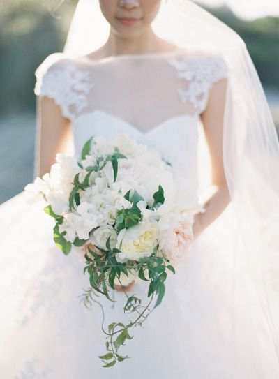 These big capped shoulders and long veil look great pared with a large and cascading white bouquet.