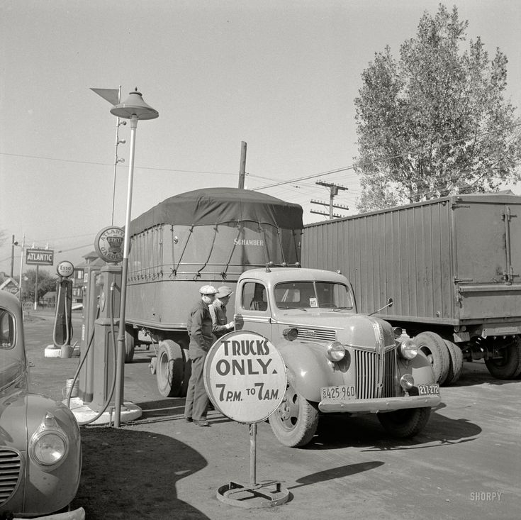 "October 1941. ""Trucks on highway en route to Utica, New York."" Decisions, decisions. Atlantic Ethyl or Esso Extra? Photo by John Collier."