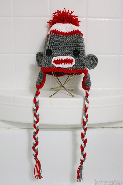 This listing is for a handmade adult size sock monkey hat in white/red/grey! I can make it with either plain red tassels or multicolored tassels (as seen in the above pictures). Please make sure to choose the correct version when ordering.  Hat is crocheted with acrylic yarn and the eyes are plastic buttons. These adult hats have a lot of stretch to them so theyre pretty much one size fits all.  If youd like this hat personalized in any way (different colors/childrens size&#x2F...
