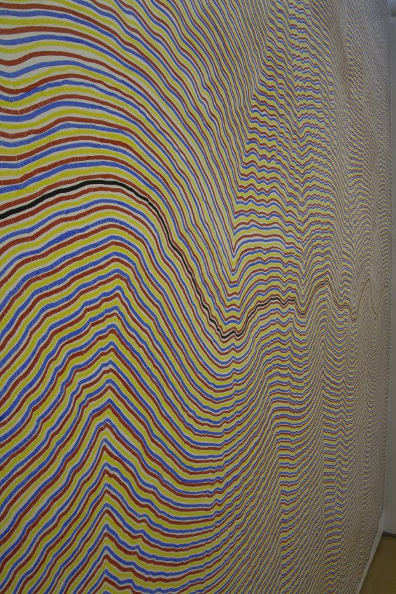 LeWitt, Sol (2001) A black not straight line is drawn at approximately the center of the wall horizontally from side to side. Alternate red, yellow and blue lines are drawn above and below the black line to the top and bottom of the wall.