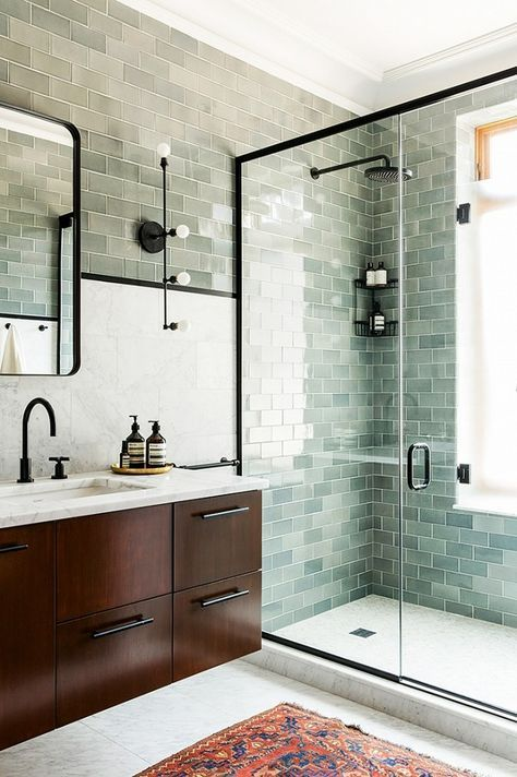 The cool green subway tiles in this Prospect Park West townhouse are complemented by a contrasting rust-colored rug. The Apparatus Studio sconces and black fixtures give the timeless space a more...