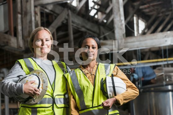 Two women with safety vests and hard hats in warehouse royalty-free stock photo