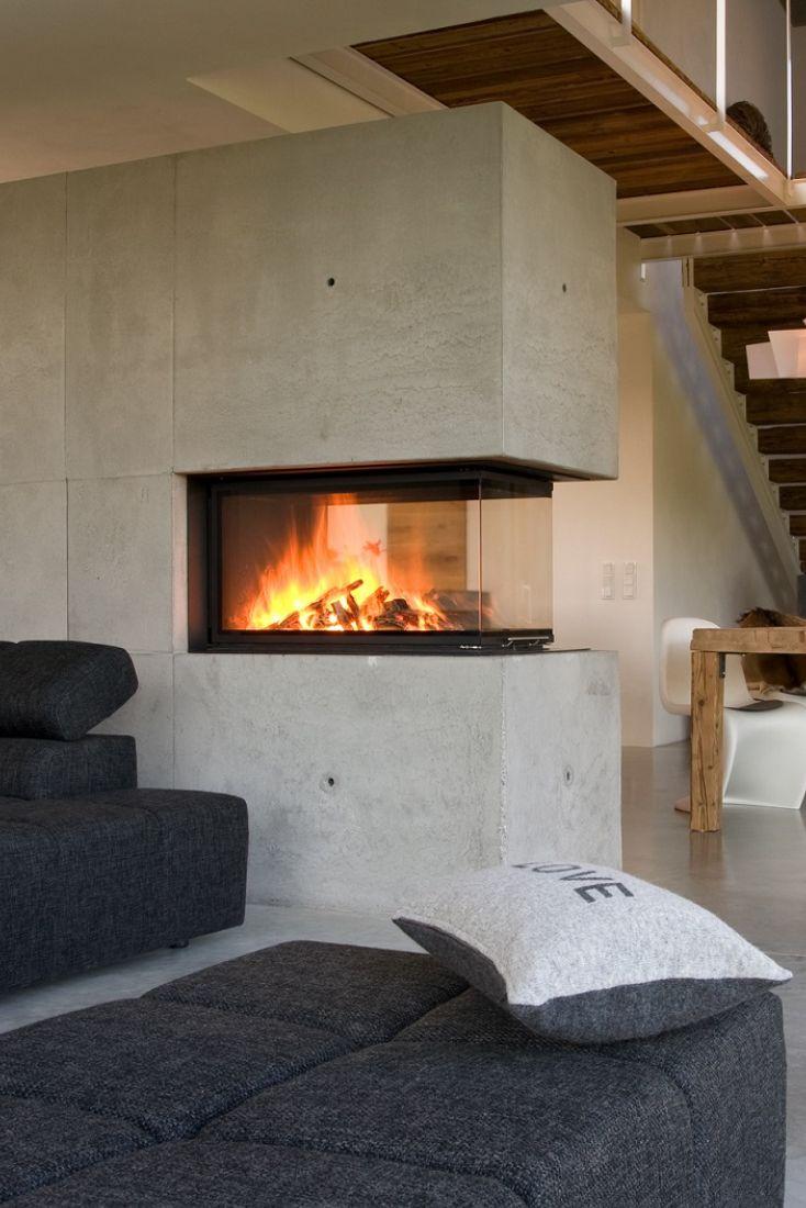Der Panorama-Kamin als Raumteiler mit Betonverklei…