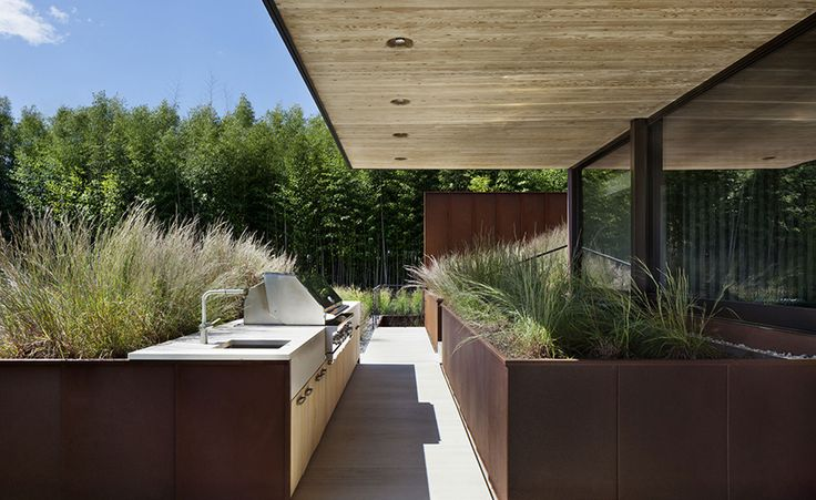 For example, the ground floor's striking wooden ceiling juts out and becomes a canopy that shades the outdoor terrace