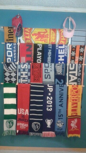 DIY soccer scarf hanger. (2 large eyelet style screws, 8 feet nylon rope, 4 dowel rods) knot the rope through the eyelets.  Create evenly spaced slip knots and insert dowels. Adjust slip knots as necessary.