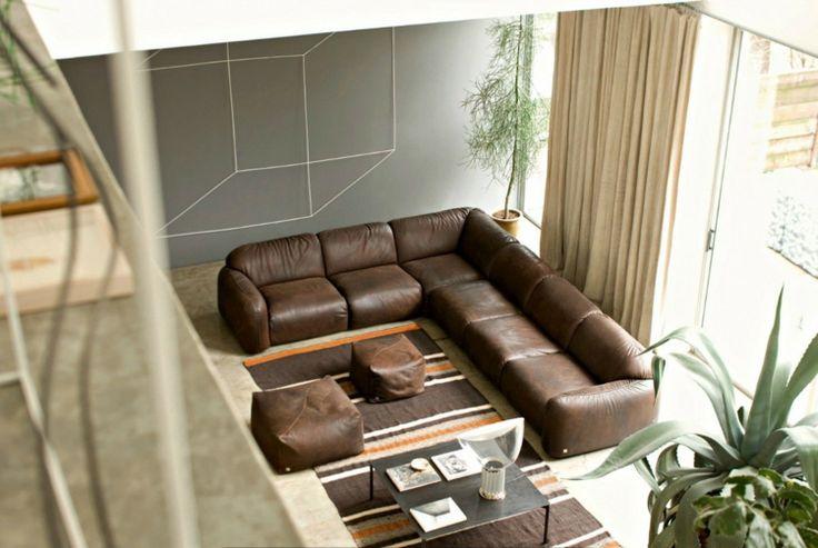 canapé d'angle en cuir marron, tapis marron à rayures blanches et orange et peinture murale grise