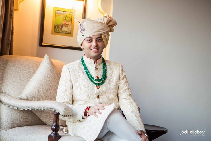 The suave and elegant groom wearing a cream, textured sherwani styled with a green gemstone necklace.