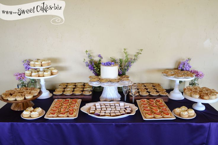 a simple wedding cake surrounded by mini cheesecakes, lemon bar bites, and a variety of individual pies