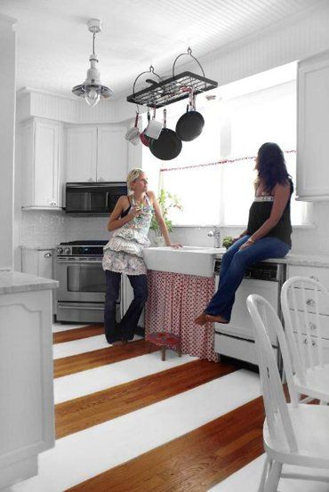 Designer Nora Fleming didn't have the budget to refinish her wood floors, so instead she strategically painted wide stripes to cover up any damaged areas.