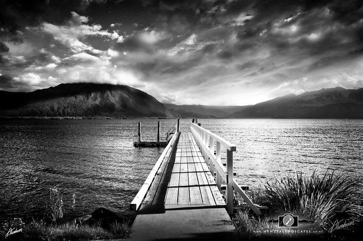 Black and white photo of Lake Brunner Jetty and Te Kinga mountain.
